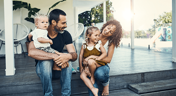 A family of four sitting on the steps of their home stock photo
